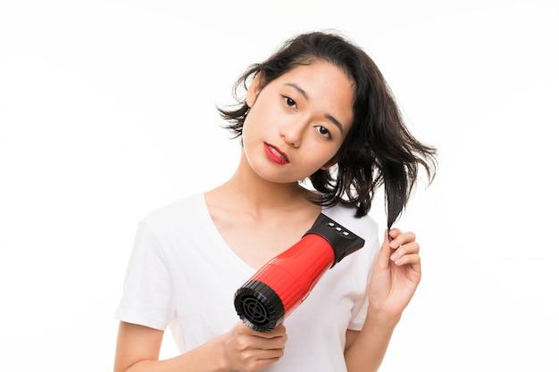 ドライヤーで孤立した壁の上のアジアの若い女性
