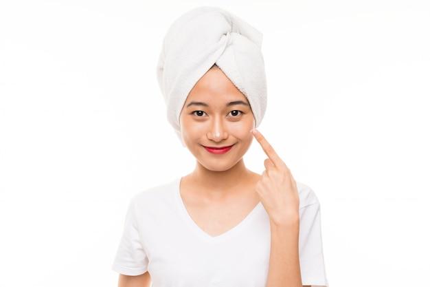 Азиатская молодая женщина над изолированной стеной с увлажняющим кремом