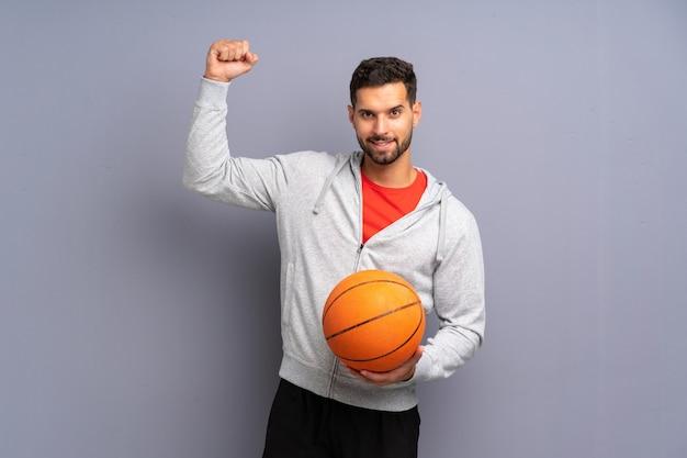 勝利を祝ってハンサムな若いバスケットボールプレーヤー男