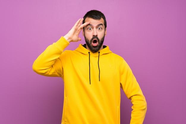黄色のスウェットシャツを持つハンサムな男はちょうど何かを実現し、解決策を意図しています