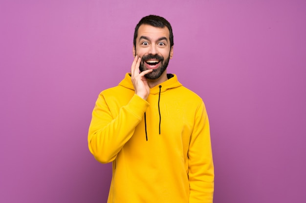 驚きとショックを受けた表情で黄色のスウェットシャツを持つハンサムな男