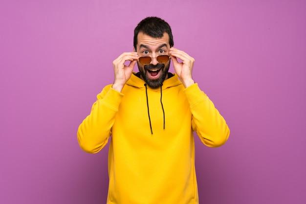 メガネと驚いた黄色のスウェットシャツを持つハンサムな男