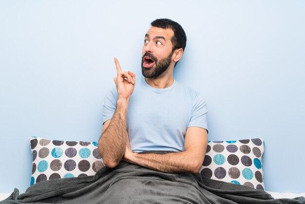 指を上向きのアイデアを考えてベッドの男