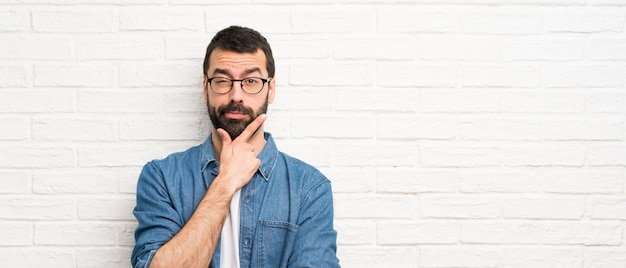 白いレンガ壁思考上のひげを持つハンサムな男
