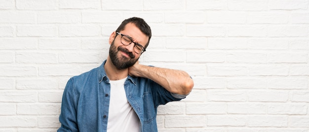 ネック痛で白いレンガの壁の上のひげを持つハンサムな男