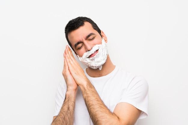 Укомплектуйте личным составом брить бороду над изолированной белой стеной, делая жест сна в достойном выражении
