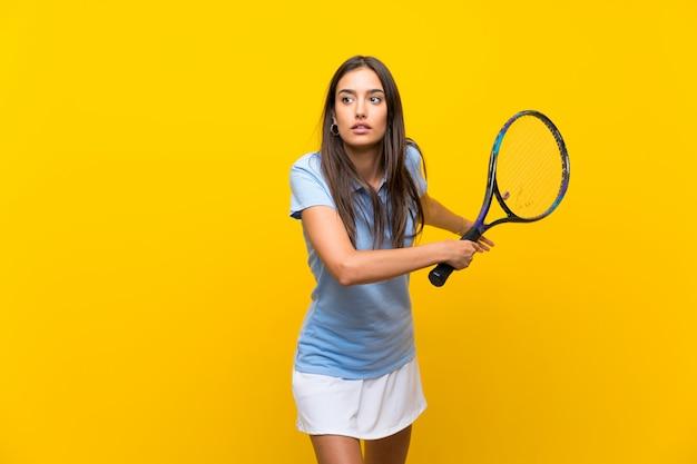 孤立した黄色の壁の上の若いテニスプレーヤー女性