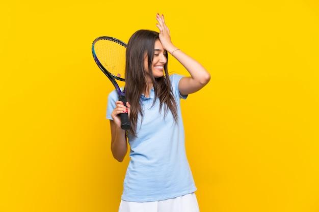 孤立した黄色の壁の上の若いテニスプレーヤーの女性は何かを実現し、解決策を意図