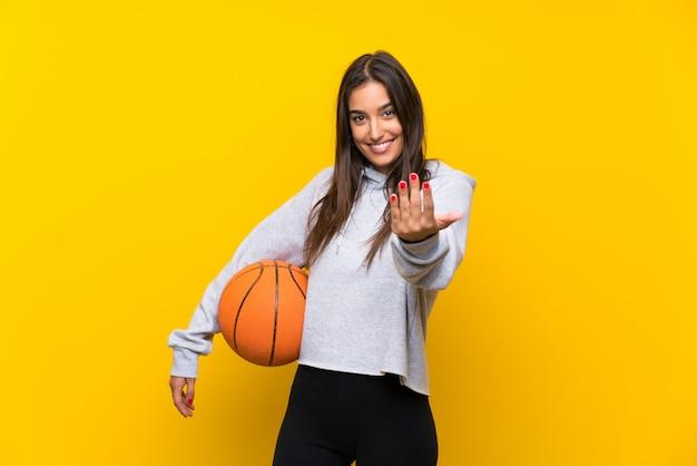 手で来ることを招待して孤立した黄色の壁でバスケットボールをプレーする若い女性。あなたが来て幸せ