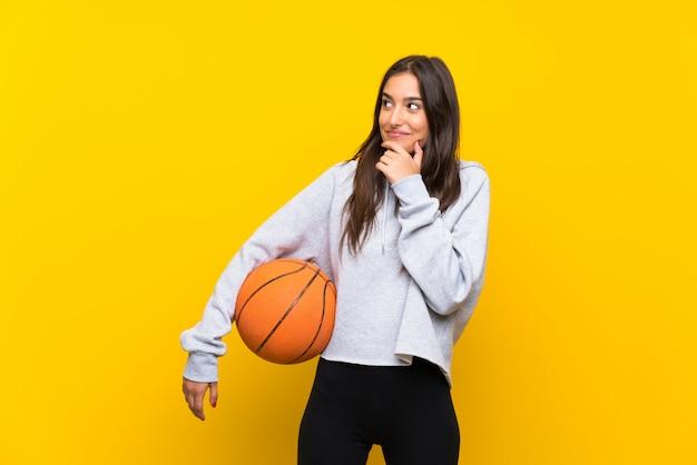 アイデアを考えて孤立した黄色の壁でバスケットボールをプレーする若い女性