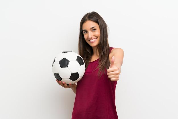 サッカーボールを保持している孤立した白い壁の上の若い女性