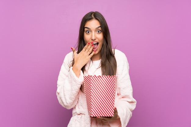 Молодая женщина в пижаме и халате над изолированной фиолетовой стеной держа попкорны