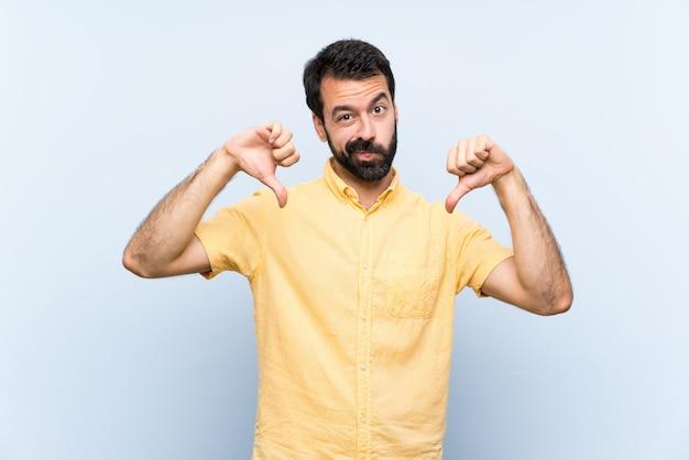 親指ダウンを示す分離の青い壁の上のひげと若い男