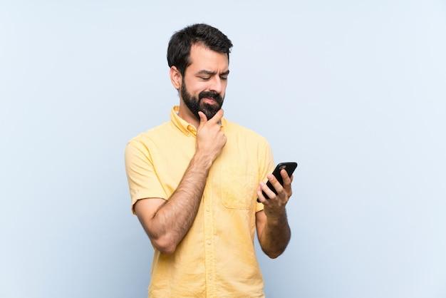 思考とメッセージを送信する分離の青い壁の上のひげと若い男