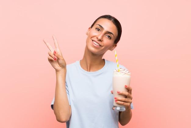 笑みを浮かべて、勝利のサインを示す分離のピンクの壁にいちごのミルクセーキを持つ若い女性