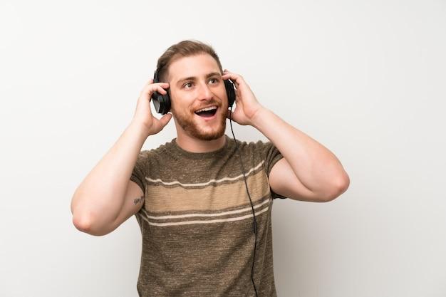 Красивый мужчина на белом фоне, слушая музыку в наушниках