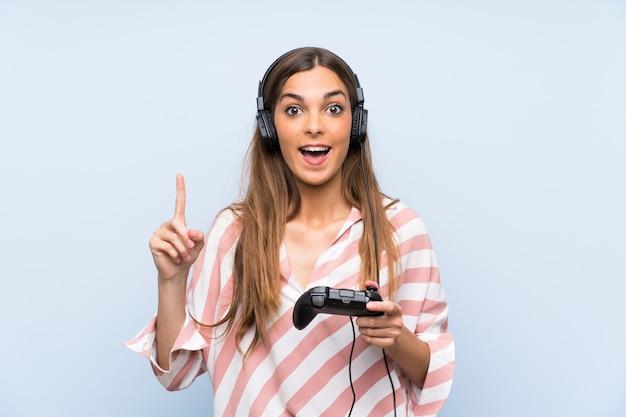素晴らしいアイデアを指している分離の青い壁の上のビデオゲームコントローラーで遊ぶ若い女性