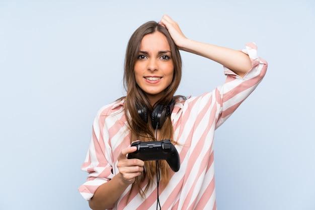 孤立した青い壁の上のビデオゲームコントローラーで遊ぶ若い女性