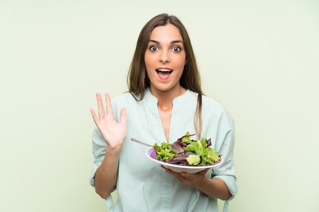 ショックを受けた表情で孤立した緑の壁の上のサラダを持つ若い女性