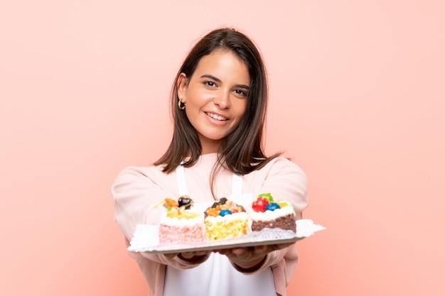 Молодая девушка держит много различных мини-пирожных над изолированной стеной