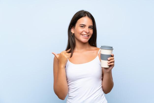 製品を提示する側を指している分離の青い壁にテイクアウェイコーヒーを保持している若い女性