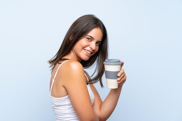 孤立した青い壁にテイクアウェイコーヒーを保持している若い女性