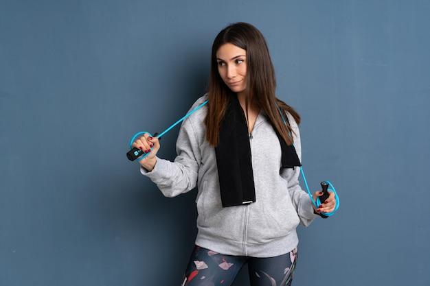 縄跳びを持つ若いスポーツ女性