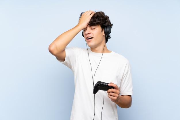 孤立した青い壁の上のビデオゲームコントローラーで遊ぶ若い男は何かを実現し、解決策を意図しています