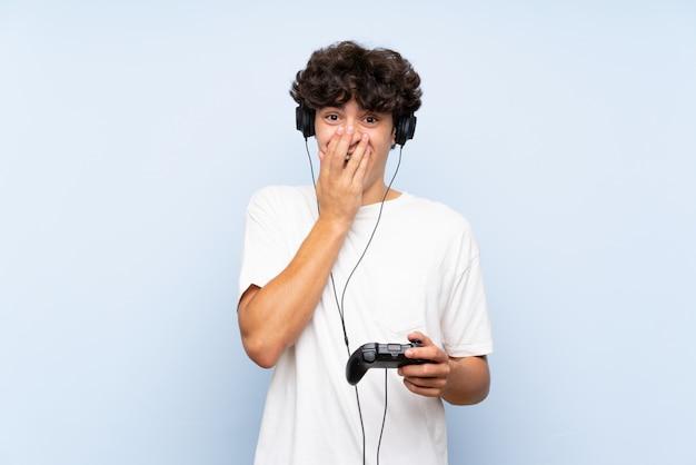 驚きの表情で分離された青い壁を越えてビデオゲームコントローラーで遊ぶ若い男
