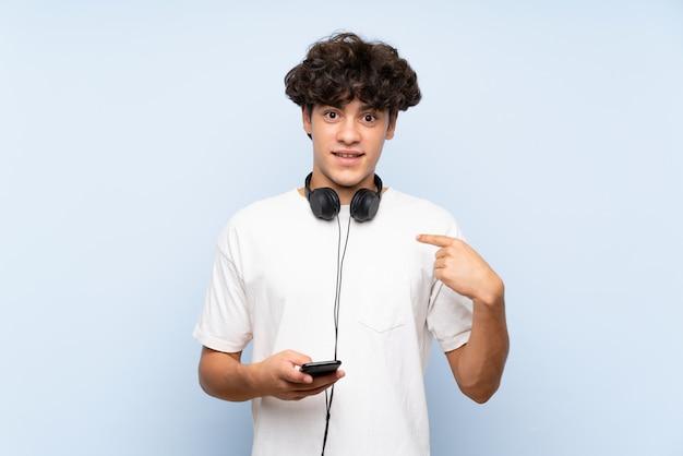 Музыка молодого человека слушая с чернью над изолированной голубой стеной с выражением лица сюрприза