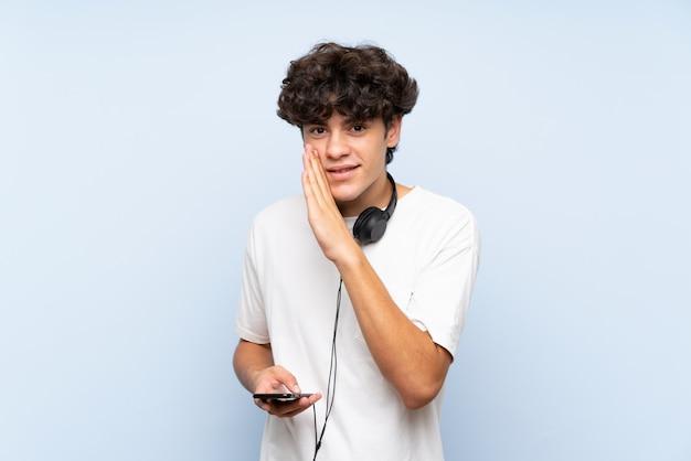 若い男が何かをささやいて孤立した青い壁の上の携帯電話で音楽を聴く