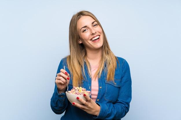 Счастливая молодая женщина с миской каш над изолированной синей стеной