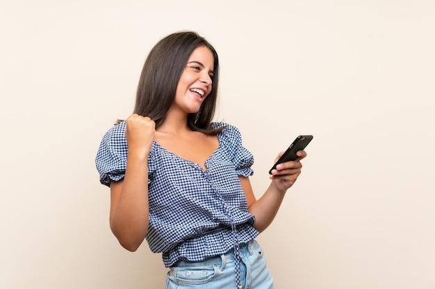 携帯電話を使用して孤立した壁の上の少女
