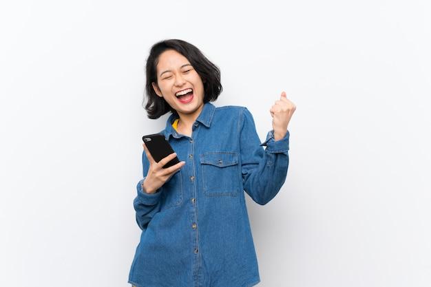勝利の位置に電話で孤立した白い壁の上のアジアの若い女性