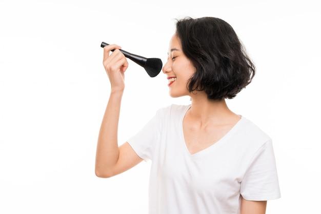 化粧ブラシで孤立した壁の上のアジアの若い女性