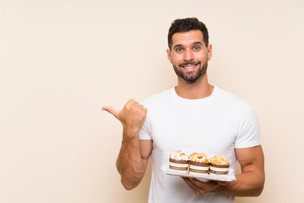 製品を提示する側を指している孤立した壁にマフィンケーキを置くハンサムな男