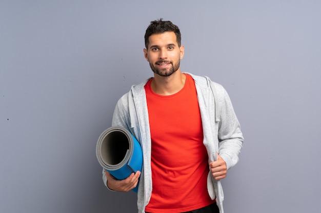 Молодой спортивный человек с ковриком
