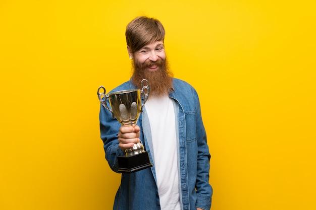 トロフィーを保持している孤立した黄色の壁の上の長いひげを持つ赤毛の男