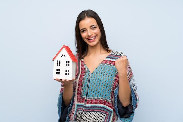 小さな家を保持している孤立した青い壁の上の若い女性