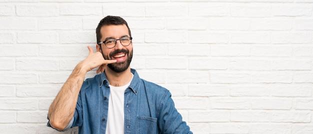 電話のジェスチャーを作る白いレンガの壁の上のひげを持つハンサムな男。コールバックサイン