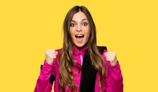 孤立した黄色の壁の上の勝者の位置で勝利を祝う若いスポーツ女性
