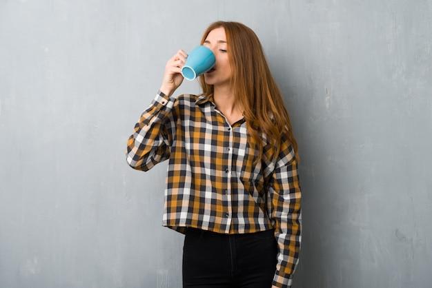 熱い一杯のコーヒーを保持しているグランジの壁の上の若い赤毛の女の子