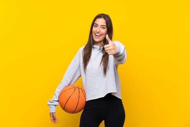 Молодая женщина играет в баскетбол на желтой стене с большими пальцами вверх, потому что случилось что-то хорошее