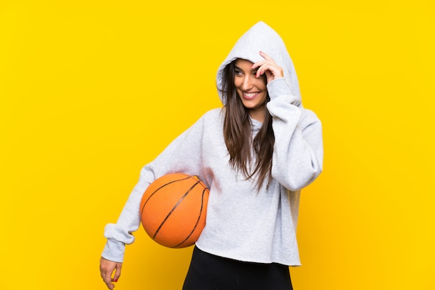 Молодая женщина играет в баскетбол на желтой стене