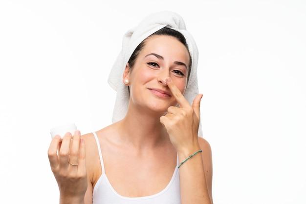 Молодая женщина с увлажняющим кремом над изолированной белой стеной