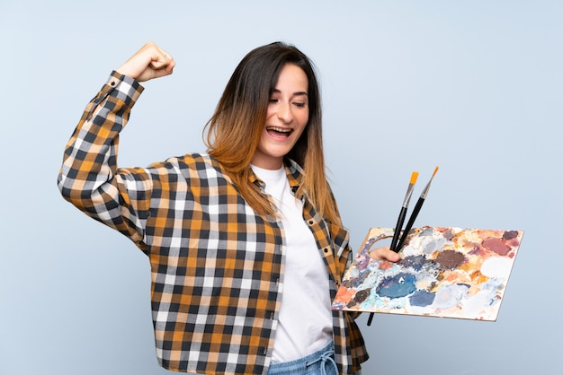勝利を祝う分離の青い壁の上の若い画家女性