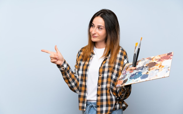 製品を提示する側を指している分離の青い壁の上の若い画家女性