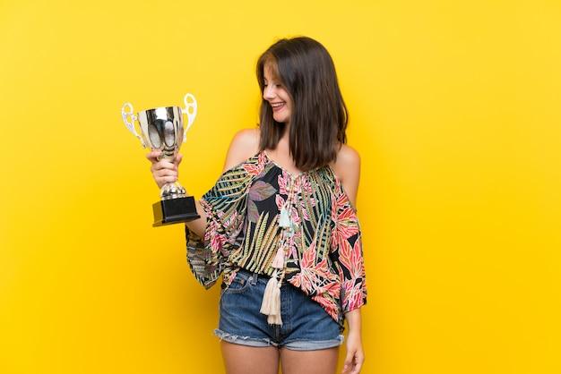 Кавказская девушка в красочном платье над изолированной желтой стеной держит трофей