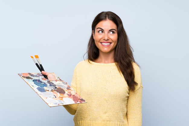 笑顔ながら見上げる孤立した青い壁の上の若いアーティストの女性
