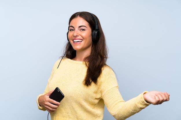 孤立した青い壁の上の携帯電話で音楽を聴くと踊る若い女性